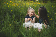 Girls sitting in wildflower meadow face to face smiling - CUF20148