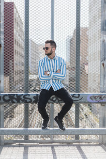 Young man sitting on fence - AFVF00585