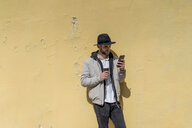 Bearded man wearing black hat, leaning on wall, using smartphone, coffee to go - AFVF00588