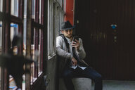 Bearded man wearing black hat, using smartphone - AFVF00597