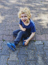 Portrait of smiling little boy dressed in blue sitting on pavement - MUF01542