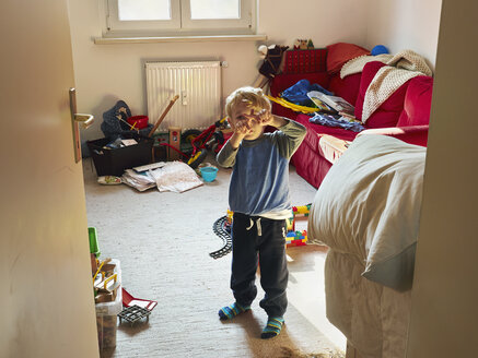 Little boy standing in his messy room building cross with his fingers - MUF01554