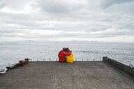 Iceland, North of Iceland, back view of couple sitting on jetty looking at view - AFVF00600