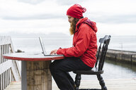 Iceland, North of Iceland, man sitting in front of the sea using laptop - AFVF00606