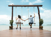 Thailand, Koh Lanta, back view of couple sitting on swings in front of the sea holding hands - GEMF02048
