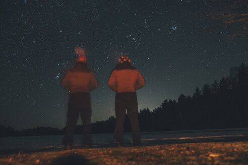 Sweden, Sodermanland, two men standing at lakeside under starry sky at night - GUSF00915