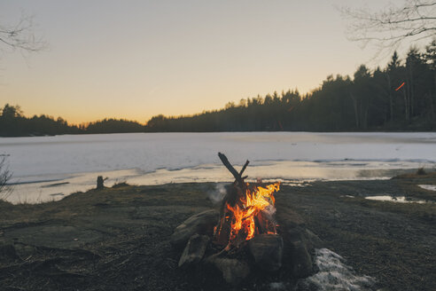 Sweden, Sodermanland, campfire at lakeside in winter - GUSF00924
