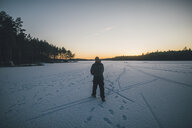 Sweden, Sodermanland, man walking on frozen lake Navsjon in winter - GUSF00930