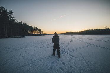 Sweden, Sodermanland, man walking on frozen lake Navsjon in winter - GUSF00930
