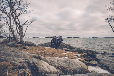 Sweden, Sodermanland, two men resting at the seashore under cloudy sky - GUSF00936