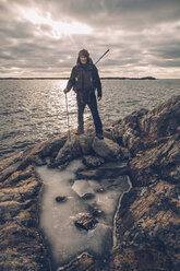 Sweden, Sodermanland, backpacker standing at the seashore under cloudy sky - GUSF00939