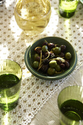Overhead view of warmed olives in bowl with white wine and water - CUF20239
