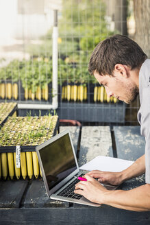 Scientist typing on laptop in plant growth research centre greenhouse - CUF20263