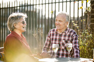 Senior couple on rooftop garden chatting and relaxing with white wine - CUF20281