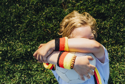 Boy in German soccer shirt lying on grass, hugging ball - MJF02312