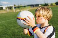 Boy with face paint and German football shirt, kissing soccer ball - MJF02315