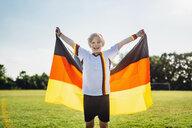 Boy, enthusiastic for soccer world championship, waving German flag - MJF02321