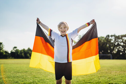 Boy, enthusiastic for soccer world championship, waving German flag - MJF02321