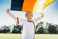 Boy, enthusiastic for soccer world championship, waving German flag - MJF02324