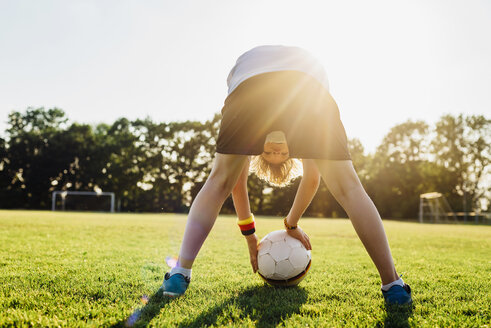 Boy on soccer field, bending over, looking through his legs - MJF02336
