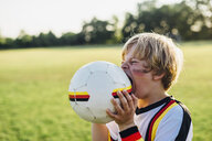 Boy with face paint and German football shirt, biting soccer ball - MJF02342