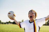 Boy wearing German soccer shirt screaming for joy, standing in water splashes - MJF02345