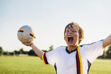 Boy wearing German soccer shirt screaming for joy, standing in water splashes - MJF02345