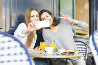 Two young female friends taking smartphone selfie at sidewalk cafe, Paris, France - CUF20469