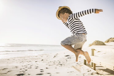 Young boy jumping on beach, wearing straw hat - CUF20523