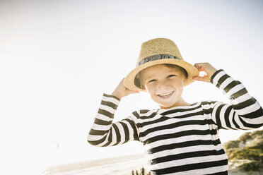 Portrait of young boy outdoors, wearing straw hat, smiling - CUF20535