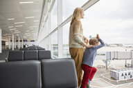 Mother and sons in departure lounge looking out of window - CUF20574