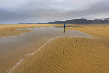 Man standing on beach, looking at view, Westfjords, Iceland - CUF20688