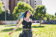 Young woman laughing and running in urban park - CUF20829