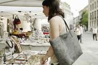 Woman looking at jewelry on market stall, Milan, Italy - CUF20850