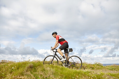 Cyclist riding past meadow - CUF20874