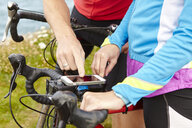 Cyclists stopping to use GPS on mobile phone - CUF20877