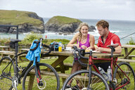 Cyclists relaxing at picnic table on hill overlooking ocean - CUF20886