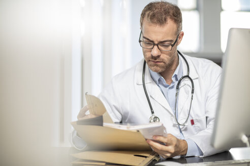 Doctor working at desk in medical practice - ZEF15504