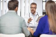 Doctor talking to couple in medical practice - ZEF15519