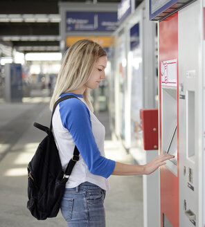 Blond woman using ticket machine at train station - BFRF01829