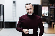 Portrait of smiling mature businessman having coffee while standing at creative office - MASF07626