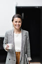 Portrait of smiling businesswoman looking away while holding coffee cup at office - MASF07665