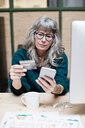 Mature businesswoman shopping online through mobile phone while having coffee at office - MASF07671