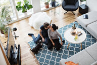 High angle view of lesbian couple kissing while sitting by dog on carpet in living room - MASF07737