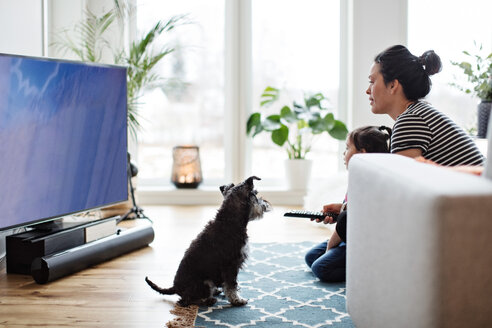 Mother and daughter watching television while sitting with dog on floor at home - MASF07767