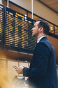 Side view of businessman looking at arrival departure board in airport - MASF07794