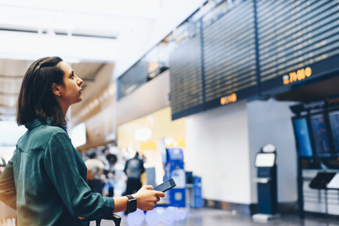 Side view of businesswoman looking at arrival departure board in airport - MASF07797