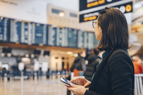 Mid adult businesswoman holding mobile phone while standing in airport - MASF07800