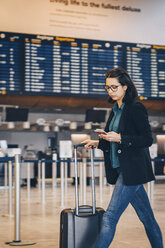 Businesswoman using mobile phone while walking with luggage in airport terminal - MASF07803