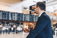 Businessman using mobile phone while looking away at airport terminal - MASF07806